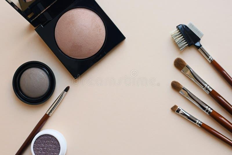 Щетки аксессуаров макияжа косметические пудрят тень глаза на сметанообразной предпосылке стоковое фото rf