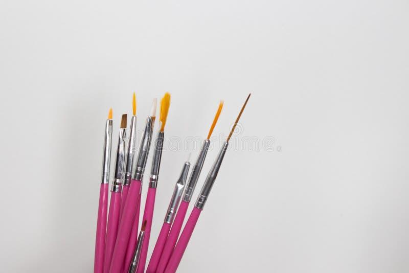 Щетки искусства ногтя на белой предпосылке, искусстве маникюра стоковая фотография