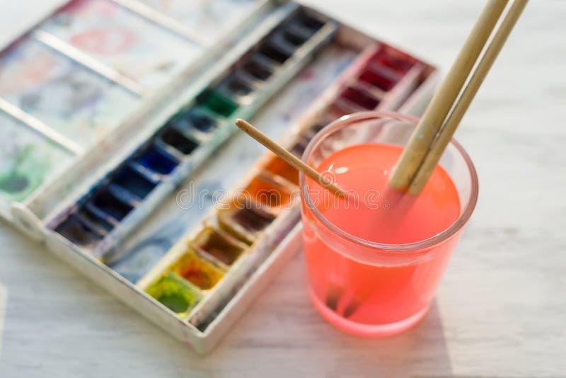 Щетки и профессиональные краски акварели на деревянном белом уступе окна стоковое изображение rf