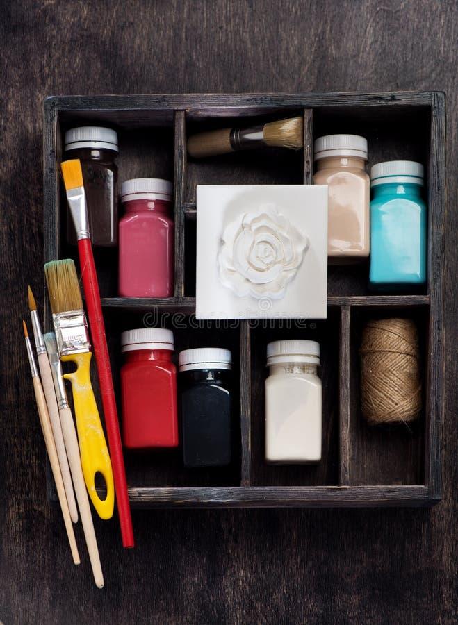 Щетки, краски для рисовать, барельеф в деревянной коробке оформителя художника, плоское положение гипсолита стоковые изображения