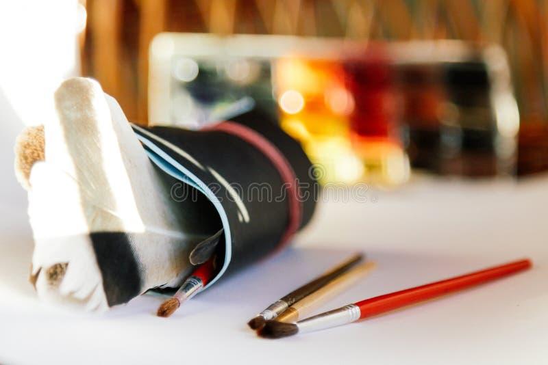 Щетки, краски и рисовальная бумага на белой предпосылке, схематические для художников и дизайнеров стоковое фото rf
