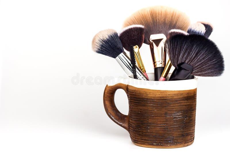 Щетки состава в керамической кружке на белой предпосылке Косметическая индустрия Щетка для красоты красивейшие женщины Детальный  стоковое изображение rf
