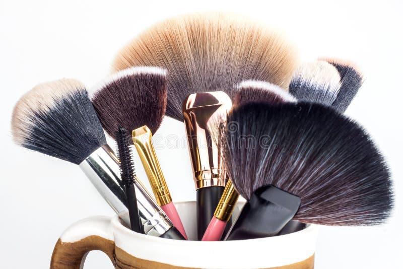 Щетки состава в керамической кружке на белой предпосылке Косметическая индустрия Щетка для красоты красивейшие женщины Детальный  стоковое фото
