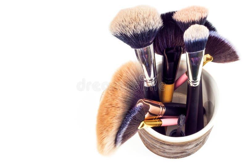 Щетки состава в керамической кружке на белой предпосылке Косметическая индустрия Щетка для красоты красивейшие женщины Детальный  стоковая фотография rf