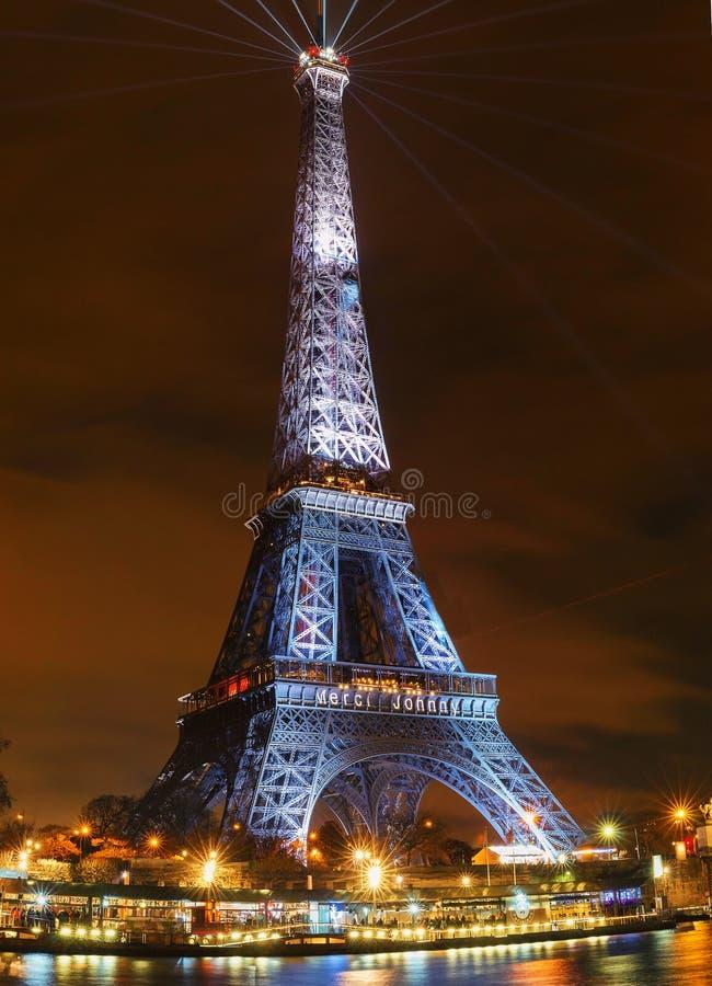 Эйфелева башня осветила вверх с сообщением Merci Джонни - спасибо Джонни в французском в Париже в утесе памяти недавно французско стоковое изображение rf