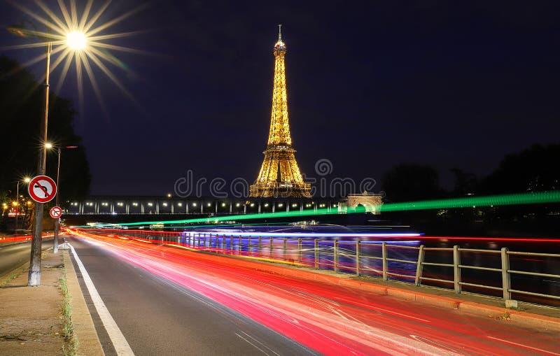 Эйфелева башня показывает свои чудесные света на заходе солнца с следами света автомобиля в Париже Оно освещено больше чем 350 ла стоковые изображения rf