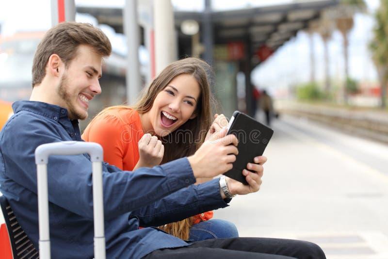 Эйфоричные пары играя игры в таблетке в вокзале стоковые изображения rf