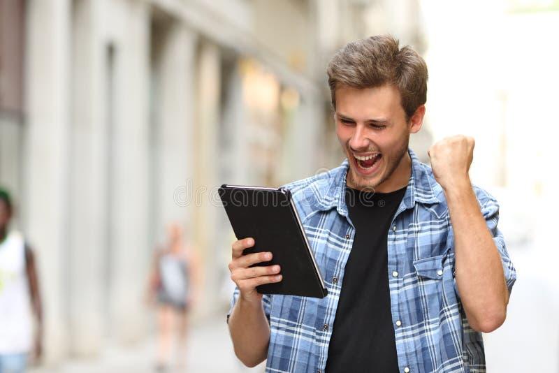 Эйфоричный человек победителя с таблеткой стоковые фото