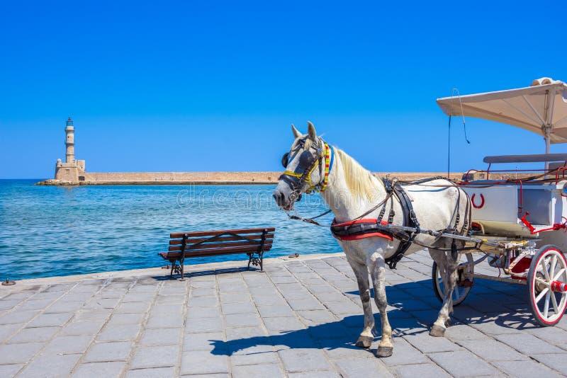Экипажи и маяк лошади на старой гавани Chania, Крита стоковые изображения