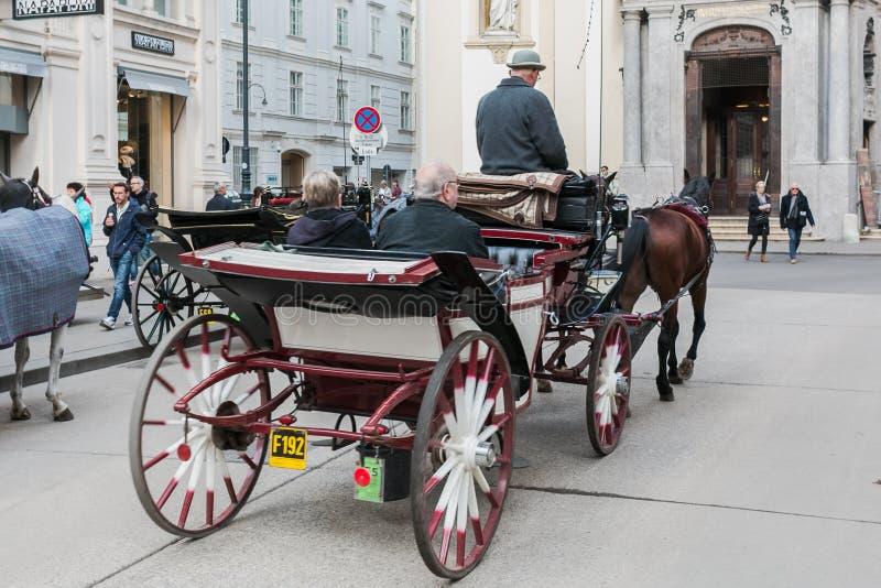 Экипаж с лошадями, водителем и туристами в Вене на экскурсионном туре вокруг города стоковое изображение