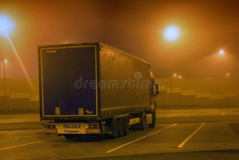 экипаж товаров дорогой, грузоперевозками - полным кораблем, туманной дорогой ночи стоковые фотографии rf