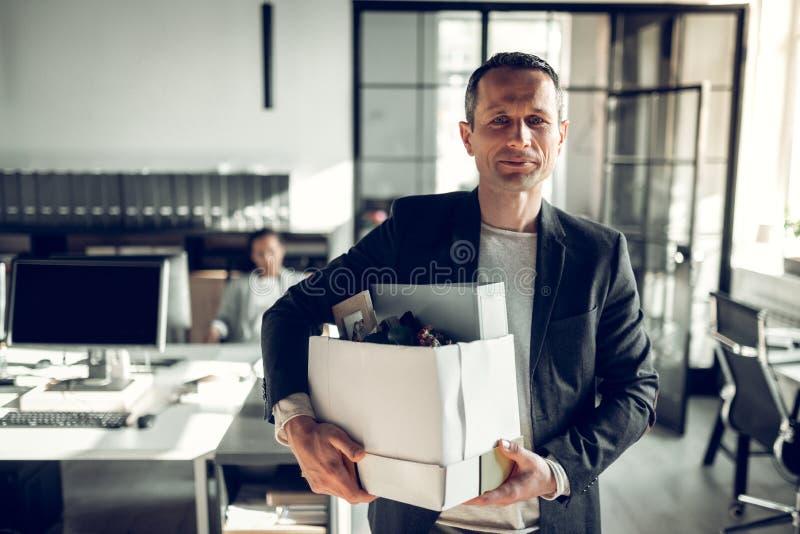 Экономист покидая офис принимая его коробку с вещами стоковое фото rf
