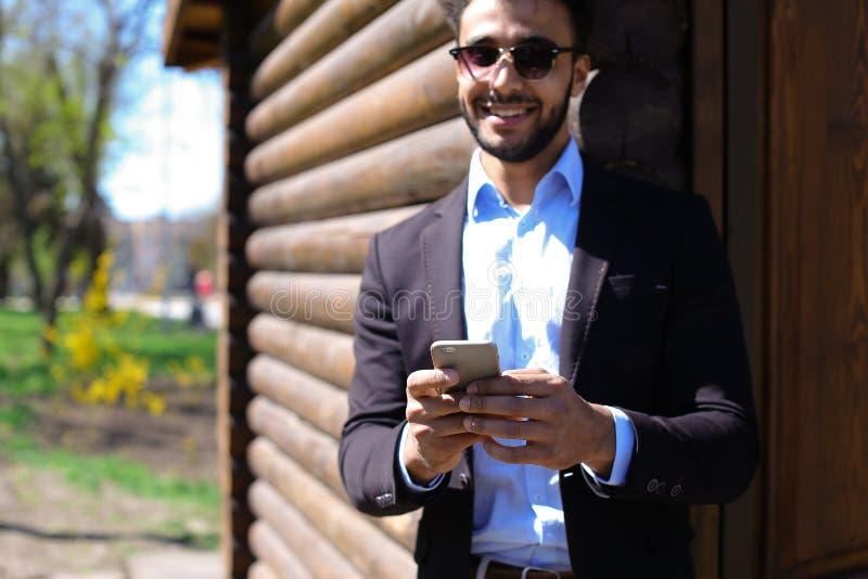 Экономист разговаривая с боссом на телефоне, усмехаясь с димплами на fa стоковое изображение