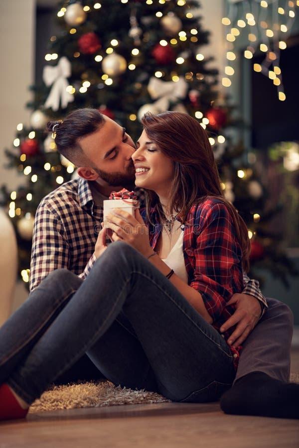 Экономно расходуйте объятие и поцелуи его жена пока дает ей рождество presen стоковое фото
