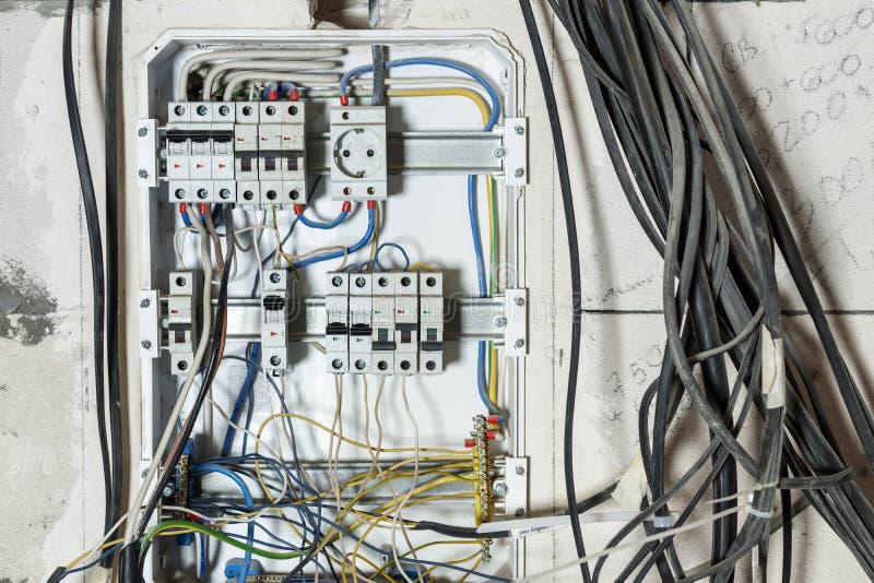 Экран в стене дома неправильное соединение, автоматическое распределение, провода запутано приведет к короткому замыканию и огню стоковое изображение