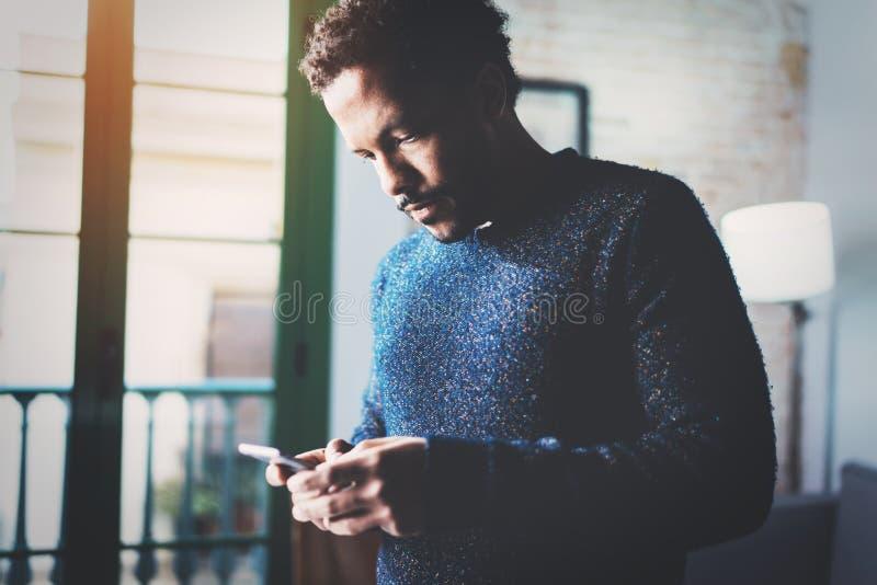 Экран задумчивого молодого африканского фрилансера печатая мобильного телефона пока работающ в новом проекте дома Смотреть чернок стоковое изображение rf