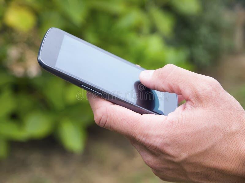 Экран руки человека касающий на франтовском телефоне 3 стоковые фото