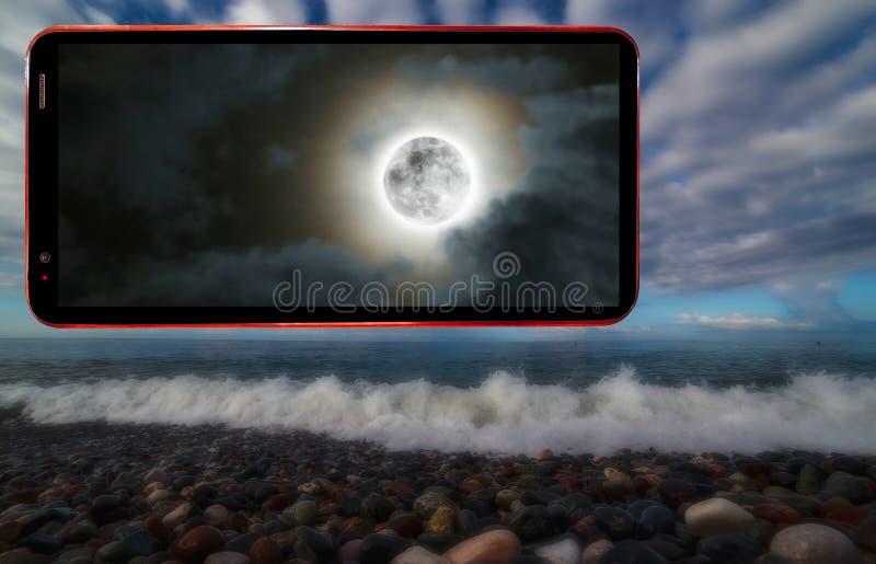 Экран сотового телефона дальше затмевает предпосылку запачканную мистикой волнистого пляжа моря с влажными камнями стоковое фото rf