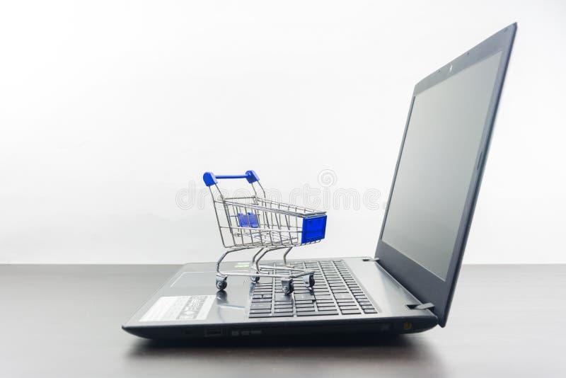 Экран тетради компьютера пустой с магазинной тележкаой на деревянной таблице стоковые фото