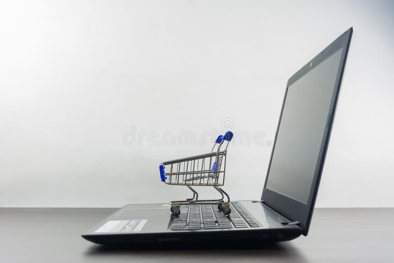 Экран тетради компьютера пустой с магазинной тележкаой на деревянной таблице стоковое изображение rf
