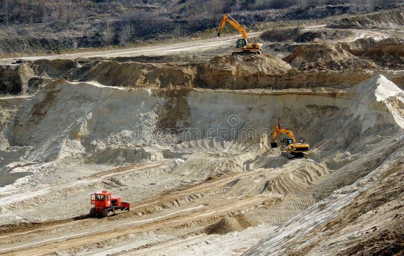 Экскаваторы извлекают глину в открытый промышленный карьер стоковая фотография rf