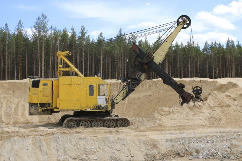 Экскаваторы на карьере песка Большой оранжевый землекоп в шахте пористого песка ждет новый перенос стоковая фотография rf