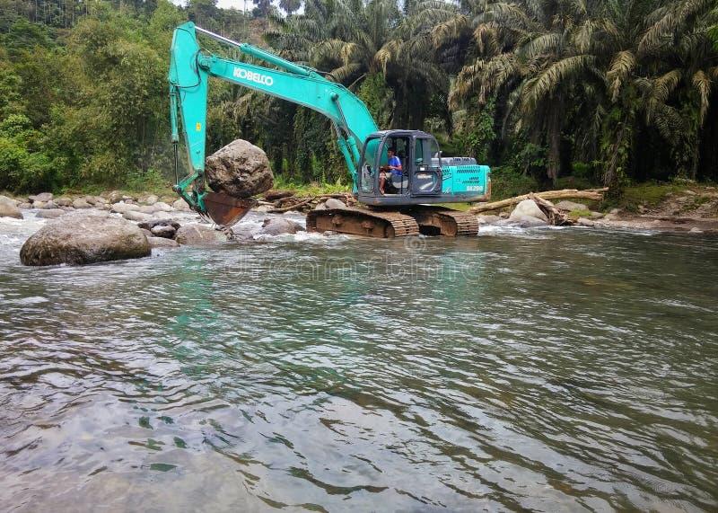 Экскаваторы работают в середине реки стоковое фото