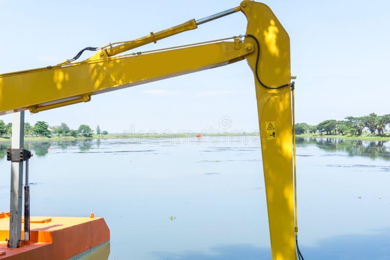 Экскаватор выкапывает край воды снова стоковое изображение rf