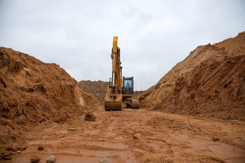 Экскаватор вытаскивает большой транш для прокладки труб Бэкхо во время земляных работ на строительной площадке Тяжелое оборудован стоковое фото rf