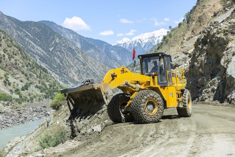 Экскаватор работая на ремонтировать дорогу, тяжелую индустрию hydraullic стоковые фото