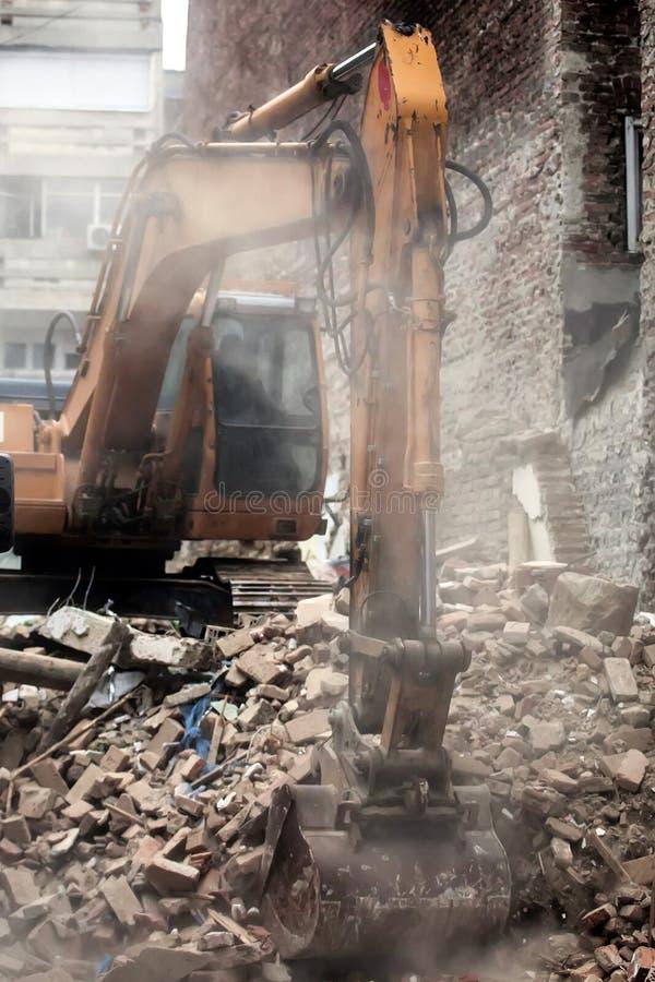 Экскаватор сокрушая старый дом стоковое фото rf
