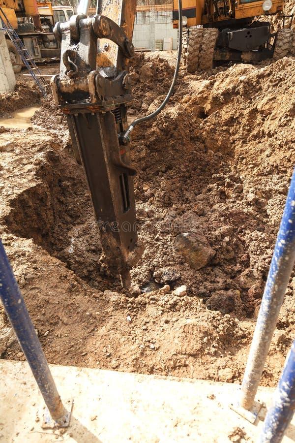 Экскаватор с jackhammer ломает утесы в земле стоковые фото