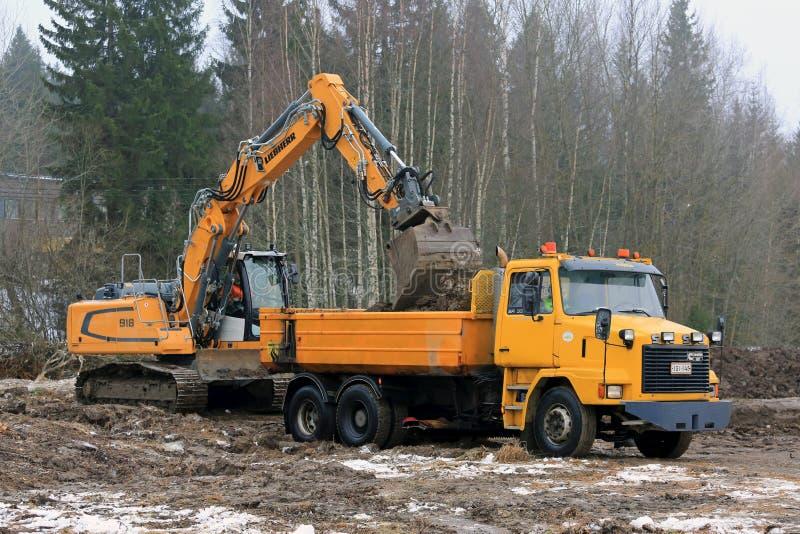 Экскаватор Crawler Liebherr нагружает грузовик подсказки Sisu SR332 стоковые изображения rf
