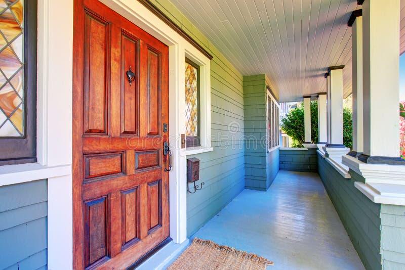 Экстерьер дома Совершенное крытое крыльцо с белыми столбцами и входной дверью стоковое фото rf