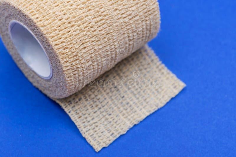 Эластичная Само-придерживаясь повязка повязки обжатия кохезионная на сини стоковое изображение