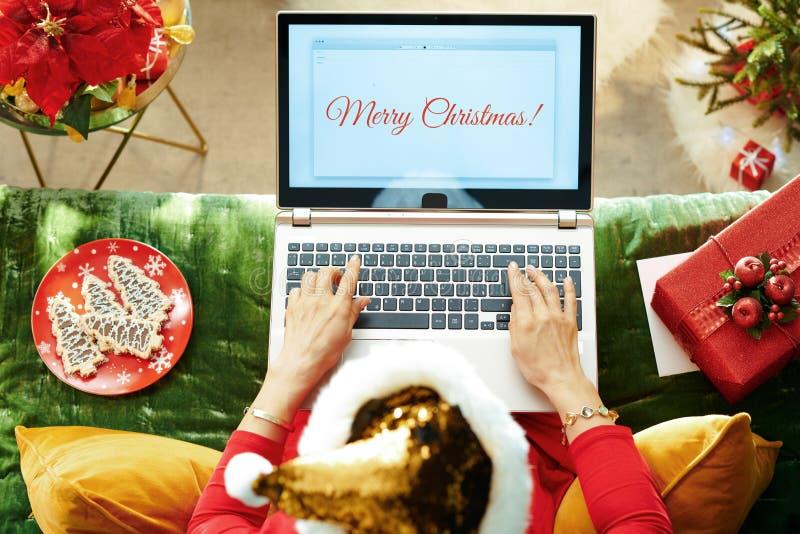 Элегантка, пишущая 'Веселое рождественское письмо' на ноутбуке стоковые изображения rf