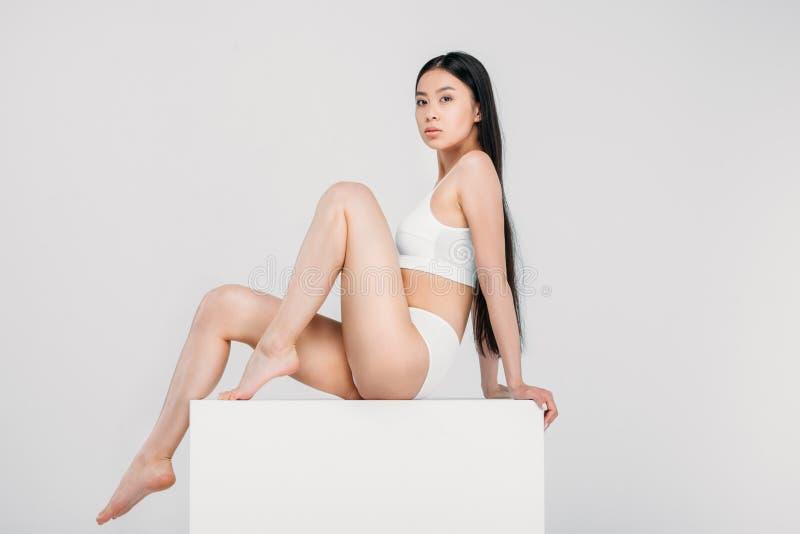 элегантная азиатская девушка представляя в женском белье на белом кубе стоковое фото