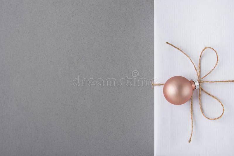 Элегантная белая подарочная коробка связанная с шпагатом с розовой смертной казнью через повешение шарика украшения Продажа насто стоковое изображение rf