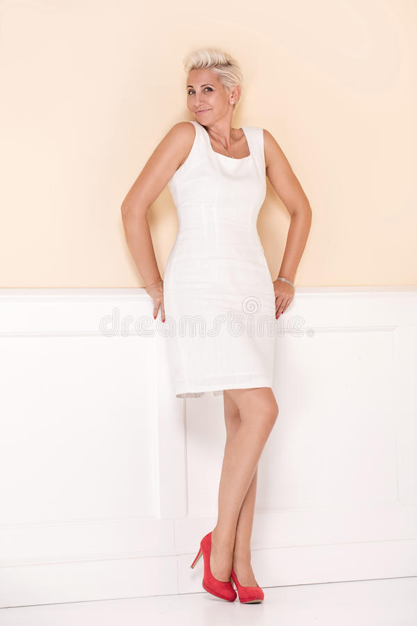 Элегантная белокурая дама усмехаясь к камере стоковые фото