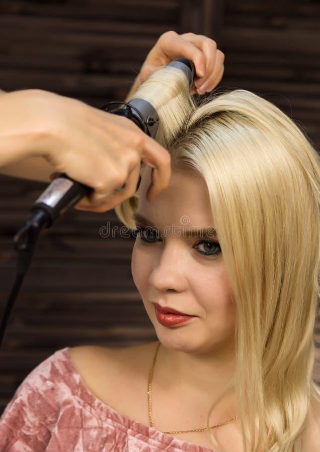 Элегантная белокурая женщина в салоне красоты Парикмахер coiffure в форме большой скручиваемости Стиль причёсок свадьбы концепции стоковая фотография