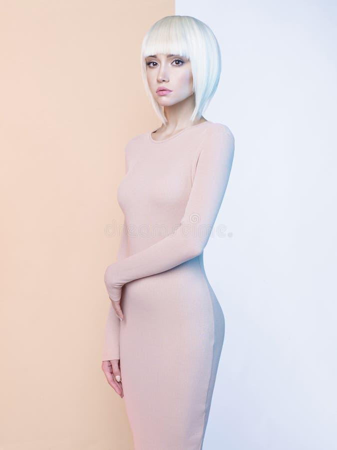 Элегантная блондинка в геометрической бежевой и белой предпосылке стоковое изображение
