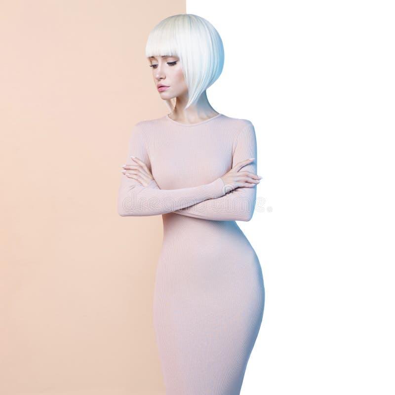 Элегантная блондинка в геометрической бежевой и белой предпосылке стоковые фото