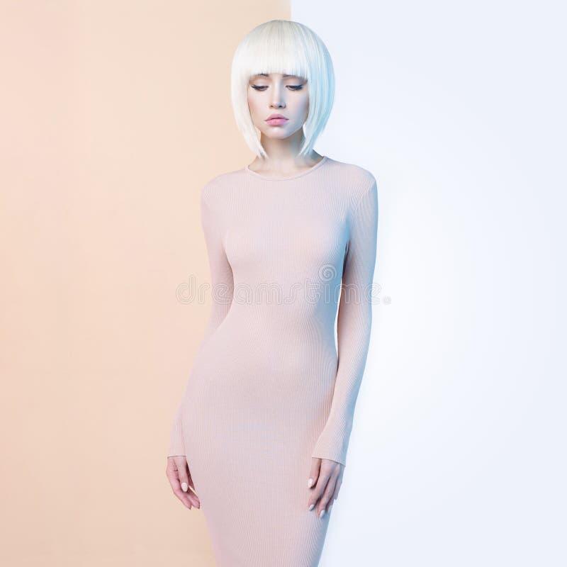 Элегантная блондинка в геометрической бежевой и белой предпосылке стоковая фотография rf