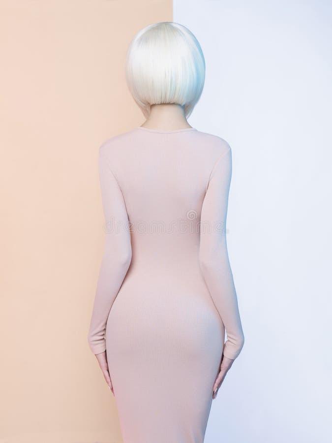 Элегантная блондинка в геометрической бежевой и белой предпосылке стоковые изображения rf