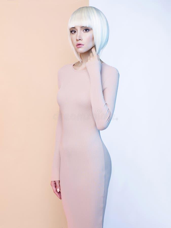 Элегантная блондинка в геометрической бежевой и белой предпосылке стоковые изображения