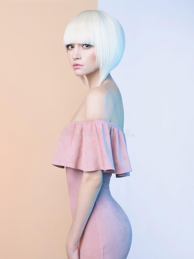 Элегантная блондинка в геометрической бежевой и белой предпосылке стоковое изображение rf