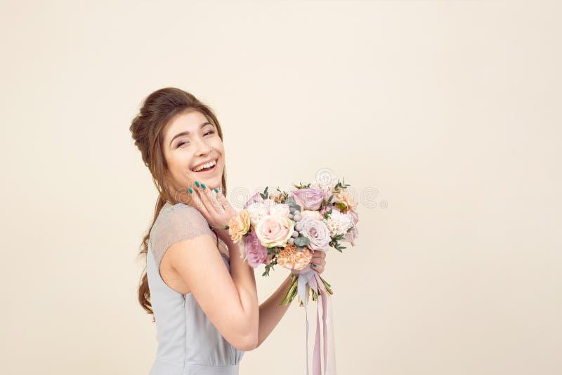 Элегантная девушка со стрижкой в мягких голубых платье и макияже держит букет стильного букета цветков стоковые изображения