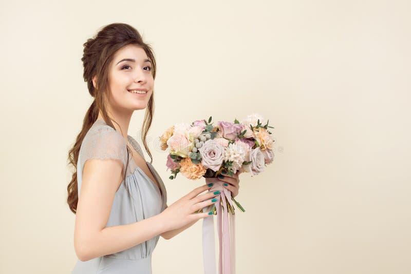 Элегантная девушка со стрижкой в мягких голубых платье и макияже держит букет стильного букета цветков стоковая фотография