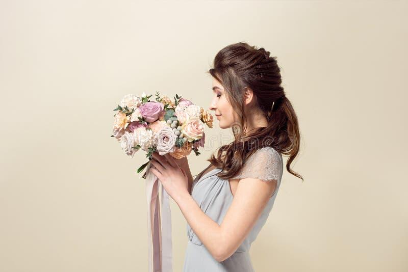 Элегантная девушка со стрижкой в мягких голубых платье и макияже держит букет стильного букета цветков стоковые фотографии rf