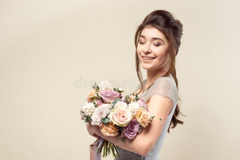 Элегантная девушка со стрижкой в мягких голубых платье и макияже держит букет стильного букета цветков стоковое фото